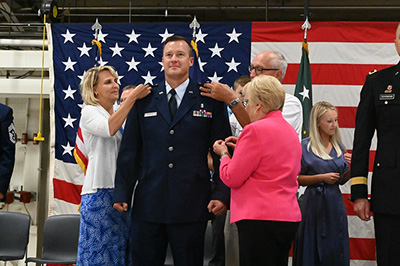 Brig. Gen. Robert A. Schulte has the rank of brigadier general pinned onto his uniform by his family members