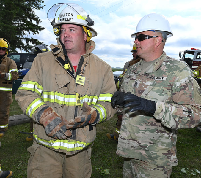 Sgt. 1st Class Benji Boll of the 188th Engineer Company, discusses search and rescue plans with Jason Sletten, the Hatton, N.D. assistant fire chief, during Exercise Vigilant Guard at Golden Lake, N.D., Aug. 5, 2020. (Air National Guard photo by Chief Master Sgt. David H. Lipp)